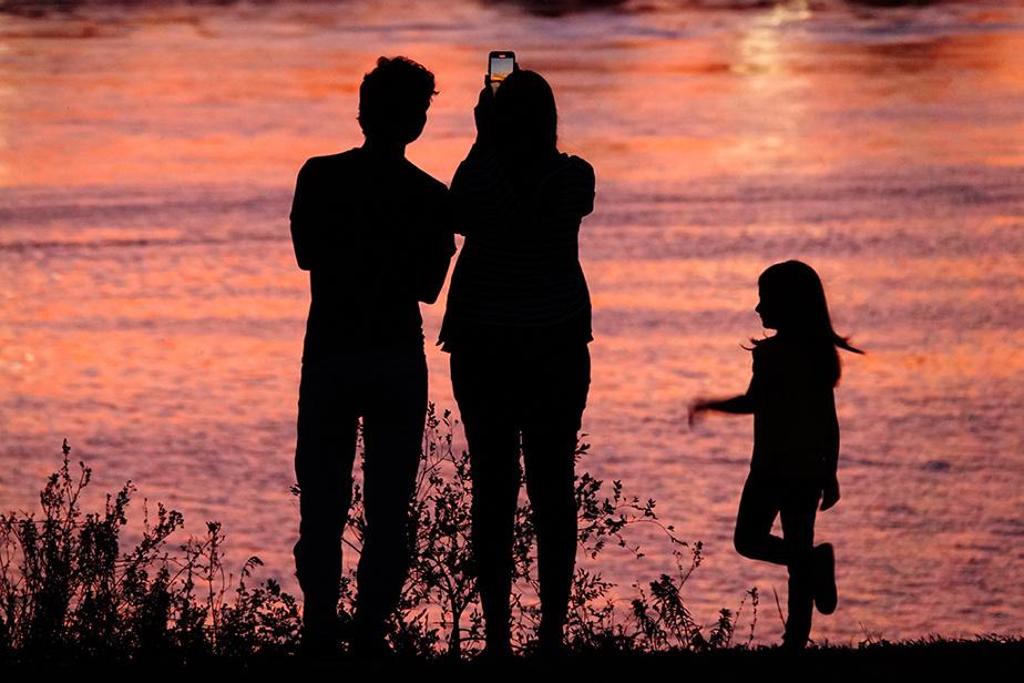 Une femme accompagnée des membres de sa famille capture le soleil couchant en photo, aux abords du Saint-Laurent, sur la Rive-Sud de Montréal.