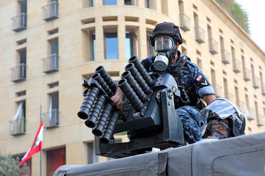 Des policiers se préparent à tirer des gaz lacrymogènes.