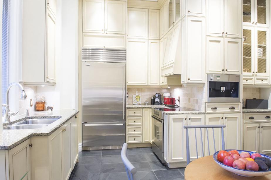 La cuisine, signée Denis Couture, inclut une table avec quatre chaises où l'on peut manger. À noter, le placard (butler's pantry) qui abrite d'autres rangements ainsi qu'un cellier. Les revêtements du comptoir sont en granite.