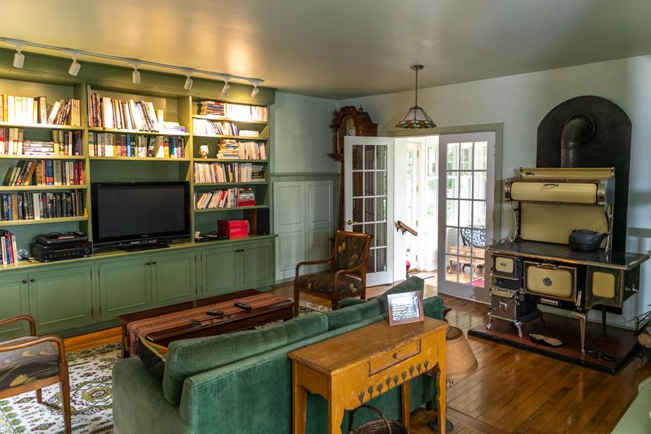 Les pièces du rez-de-chaussée sont en enfilade. Celle-ci est logée entre la cuisine et la nouvelle verrière à l'avant de la maison. À la droite, le solarium. On croit que cette pièce pouvait être l'ancienne cuisine en raison de l'ancien poêle à bois qui fonctionne toujours.