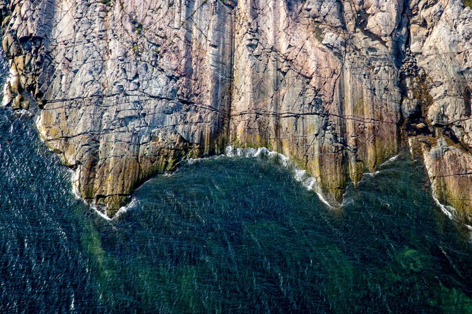 Des parois rocheuses infiltrées de lignes droites se jettent dans le fleuve à la hauteur des îlets Jérémie, sur la Côte-Nord.