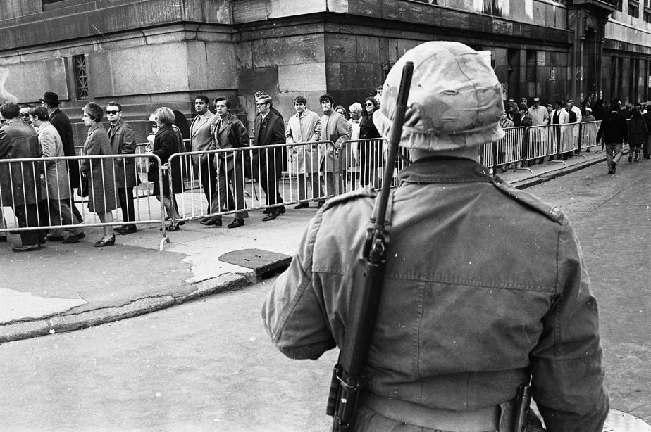 En pleine crise d'Octobre, en 1970, la foule défile sous le regard d'un soldat de l'armée canadienne, pour la signature du registre en l'honneur du ministre Pierre Laporte.