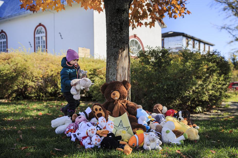 Plusieurs enfants, amis des petites victimes, sont venus spontanément déposer des peluches, au pied d'un érable près de l'église.