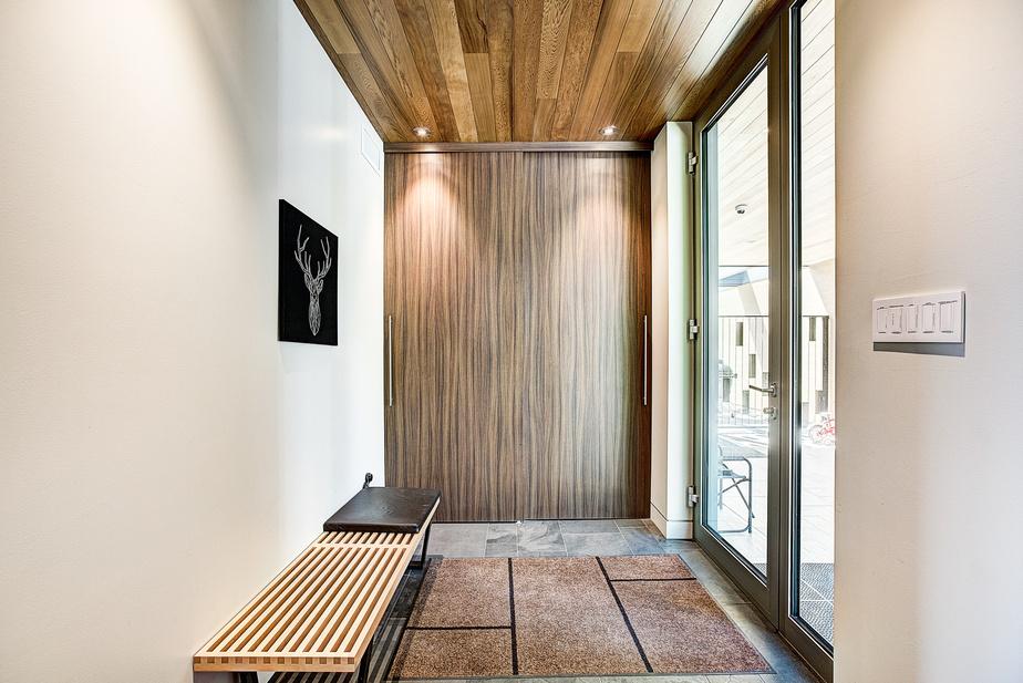 Le garde-robe de l'entrée est fermé par des portes en stratifié au fini bois que l'on retrouve partout dans la maison.