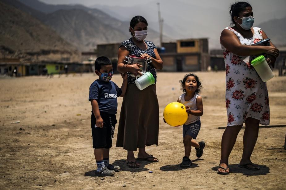 Des Péruviennes et leurs enfants patientent pour obtenir un repas devant la cuisine collective de Comas.