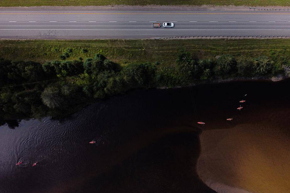 Des plaisanciers en kayak ou en planche à pagaie naviguent sur la rivière Rouge, à quelques mètres de la route117 à La Conception.