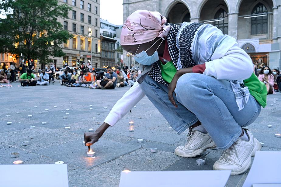 Une femme allume une chandelle sur la place d'Armes, à Montréal, lors d'une veillée organisée à la mémoire des 215enfants autochtones morts dont les restes ont été récemment retrouvés dans des fouilles sur le terrain du pensionnat autochtone de Kamloops, en Colombie-Britannique.
