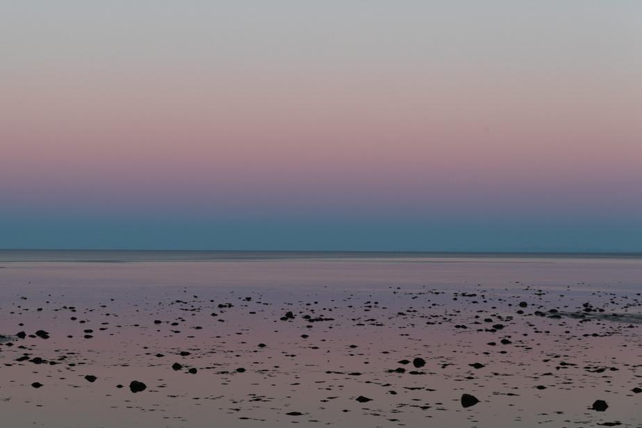 Les derniers rayons de soleil pointent derrière l'horizon. Le fleuve reflète la palette de couleurs pastel qui emplit le ciel.