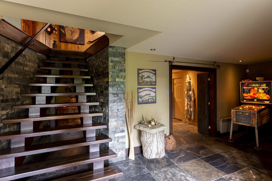Au premier niveau se trouvent l'entrée principale, un vaste vestibule, un bureau et une salle de lavage. C'est là que les deux agents de bord mettaient leurs valises et nettoyaient leurs vêtements au retour d'un vol. La structure en acier de l'escalier a été réalisée par un artisan. Le monter et le descendre tient en forme, constatent les propriétaires en riant.
