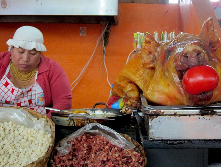 Cette femme vend du mote (maïs bouilli) et du porc au marché d'Otavalo.