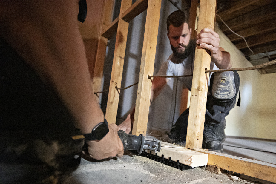 Connor Hall (de face) et David Comeau installent la lisse ventilée Teksill à la base d'un futur mur, dans le sous-sol. Le bois ne touchera jamais au béton froid et humide.