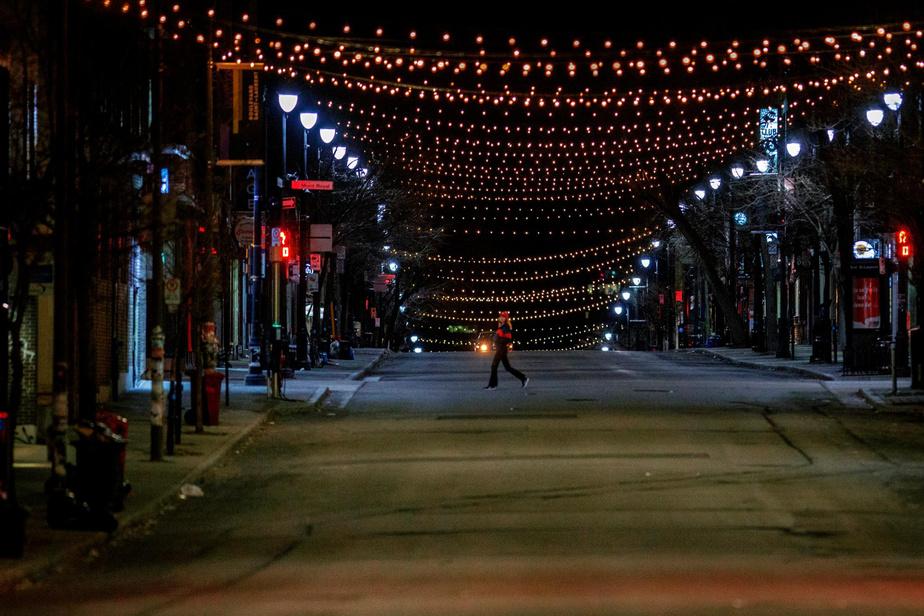 00h19: la nuit est tombée sur la ville quand la journée du 6avril2020 débute. Une personne traverse le boulevard Saint-Laurent, à l'angle de l'avenue du Mont-Royal.
