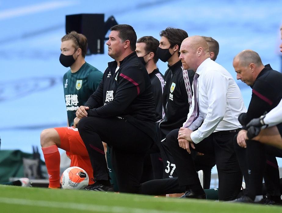 Le personnel d'entraîneurs de Burnley s'agenouille avant le début de leur match contre Manchester City