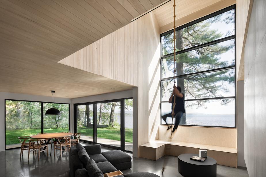 Une corde d'escalade a été installée dans l'espace où le plafond a une double hauteur, contribuant à rendre le salon «public» encore plus ludique.