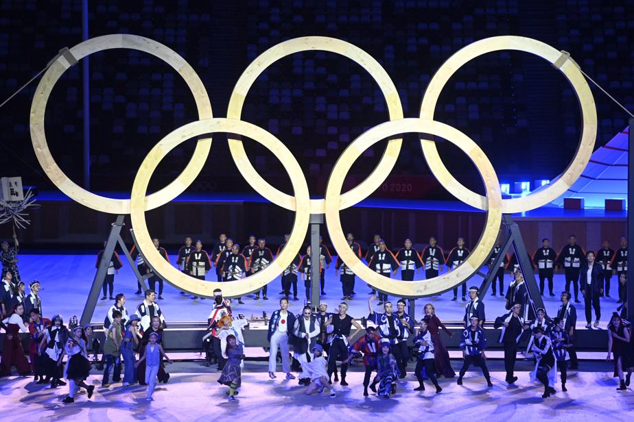 Danseurs, chanteurs et acrobates en costumes traditionnels ont hissé des anneaux olympiques en bois au centre du stade.