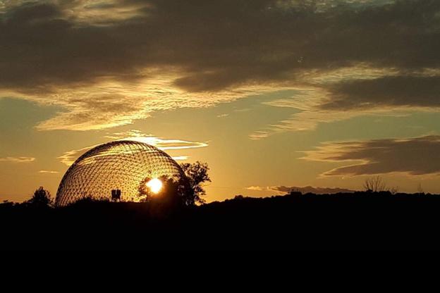 Depuis Longueuil, la vue du soleil se couchant sur Montréal reste un secret mal gardé, surtout quand la boule de feu rencontre la boule d'acier de la Biosphère.