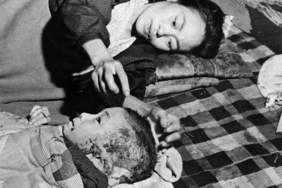 Couchée sur le sol d'un hôpital de fortune, une mère tente de réconforter son enfant blessé.