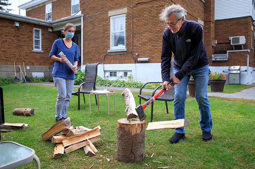Léo Héroux, 78ans, fend du bois sous la supervision de Charlotte Berjon, coordonatrice de la Maison Carpe Diem.