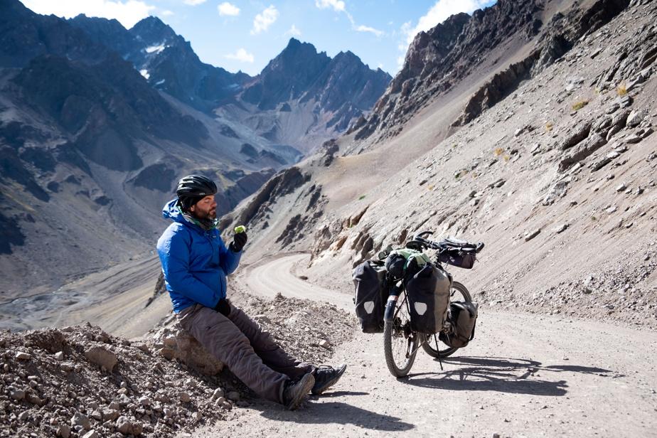 """Jonathan B. Roy a parcouru le monde à vélo, explorant une quarantaine de pays. Il a raconté une partie de son périple dans LaPresse, en 2017. Au bout du monde, on s'habitue à tout, explique-t-il. Le voici en train de savourer une pomme sur une route de montagne, entre le Chili et l'Argentine. «Je trouve la """"vie ordinaire"""" bien plus compliquée, depuis que je suis revenu au pays pour cause de pandémie!», dit-il."""