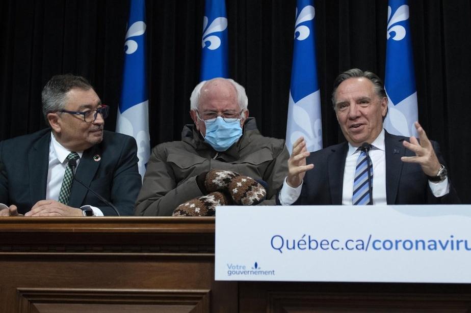 Image aux couleurs locales, Bernie prenant place aux côtés du DrArruda et du premier ministre Legault à la conférence de presse du gouvernement. Dans le fond, le Vermont, ce n'est pas siloin.