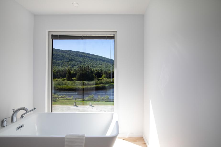 La baignoire carrée de cette maison à Stoneham, qui peut se louer sur le site de Monsieur Chalets, a vue sur la rivière Jacques-Cartier.