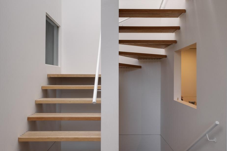 L'escalier fait de planches de chêne laisse pénétrer la lumière venue du toit dans toute la maison. L'ouverture à droite donne sur le bureau. Celle de gauche, sur une chambre d'enfant.