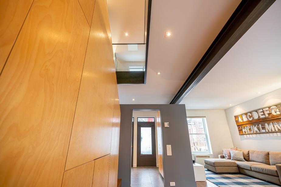 Trois astuces pour accentuer l'effet de grandeur: la cloison du vestibule qui ne rejoint pas le plafond, le puit de lumière à l'étage et l'utilisation de garde-corps en verre.