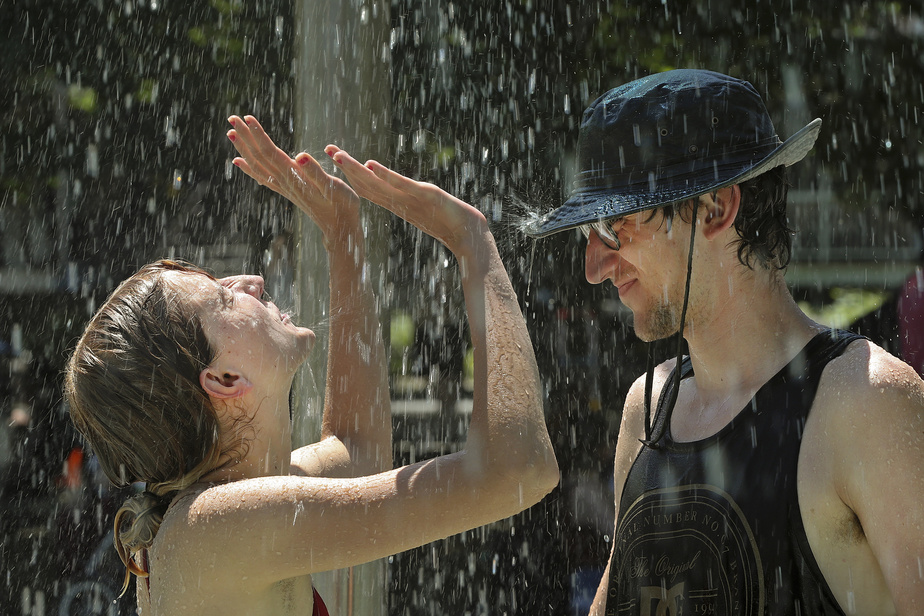 InèsThomas et MaximilienPanchon s'offrent un répit de la canicule dans les jeux d'eau du parc De Normanville, à Montréal.