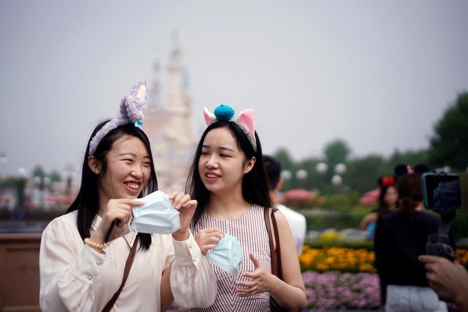 Des touristes enfilent un masque pour entrer à Disneyland, à Shanghaï, au premier jour de sa réouverture.