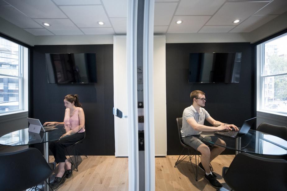 Une fois la cloison déployée, deux personnes peuvent travailler séparément sans se déranger, dans cette pièce du complexe St Ann, dans Griffintown. Myriam Harchaoui et Mathieu Léonard sont ainsi chacun dans leur bulle.