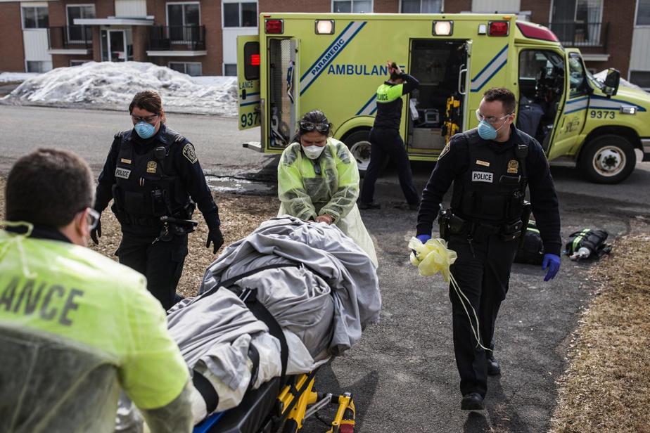 Les policiers Alexandre Després et Mélissa Lessard aident les paramédicaux Marie Kim White, Line Laurin et Dany Rodrigues à sortir le corps d'une femme âgée morte seule dans son appartement.