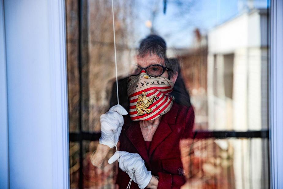Dans cette photo d'une dame âgée à la fenêtre, on aperçoit la silhouette de notre photographe, son fils.