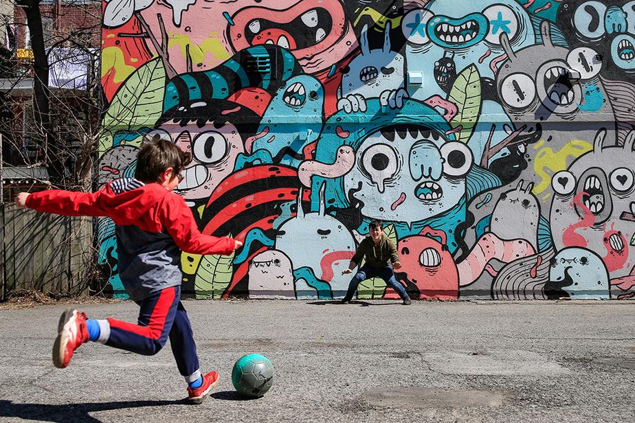 Devant une murale créée par l'artiste Astro, Matt Burghardt et son fils Luca jouent au soccer dans un stationnement de Verdun.