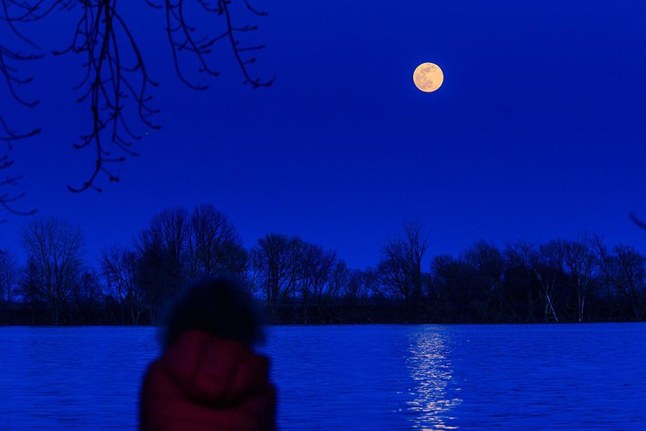 Une résidante de Pointe-aux-Trembles admire le lever de la super lune du 7avril2020, au-dessus de l'île Sainte-Thérèse.