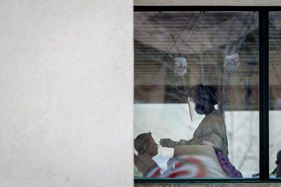 Une employée nourrit un patient au CHSLD Herron de Dorval, où il y a eu une éclosion de COVID-19.