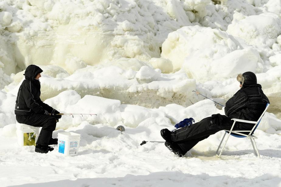 Un couple de pêcheurs s'est installé sur le bord de la rive, où les marées montent et descendent de plusieurs pieds par jour, ce qui crée un imposant mur de glace.