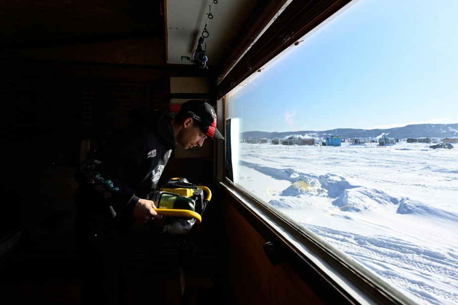 Mathieu Langelier creuse un trou dans sa cabane de pêche.