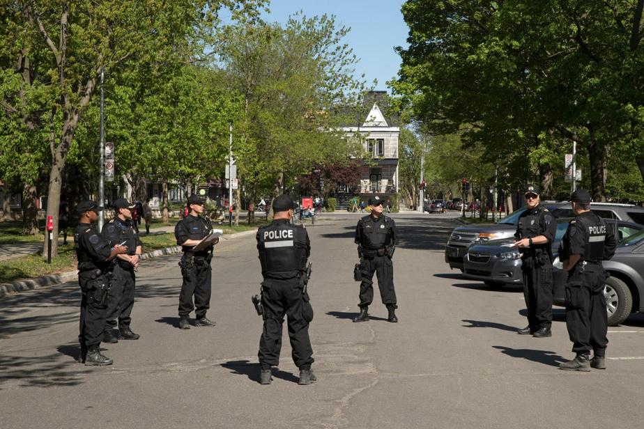 Des policiers participent au breffage du déroulement de la journée, dans un stationnement de l'avenue Calixa-Lavallée, en plein cœur du parc LaFontaine, à Montréal.