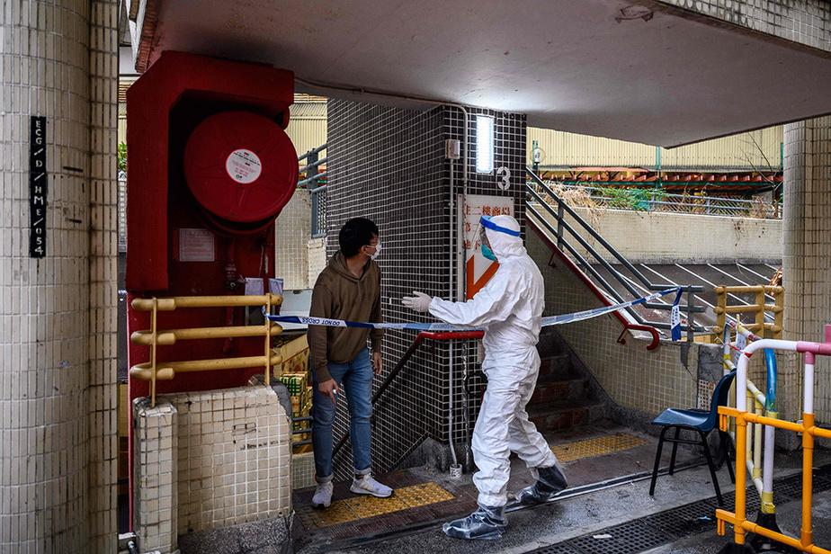 Des membres des services sanitaires encombinaison intégrale blanche étaient à pied d'œuvre mardi pour vérifier si l'épidémie s'était propagée davantage dans cette résidence abritant 3000personnes.