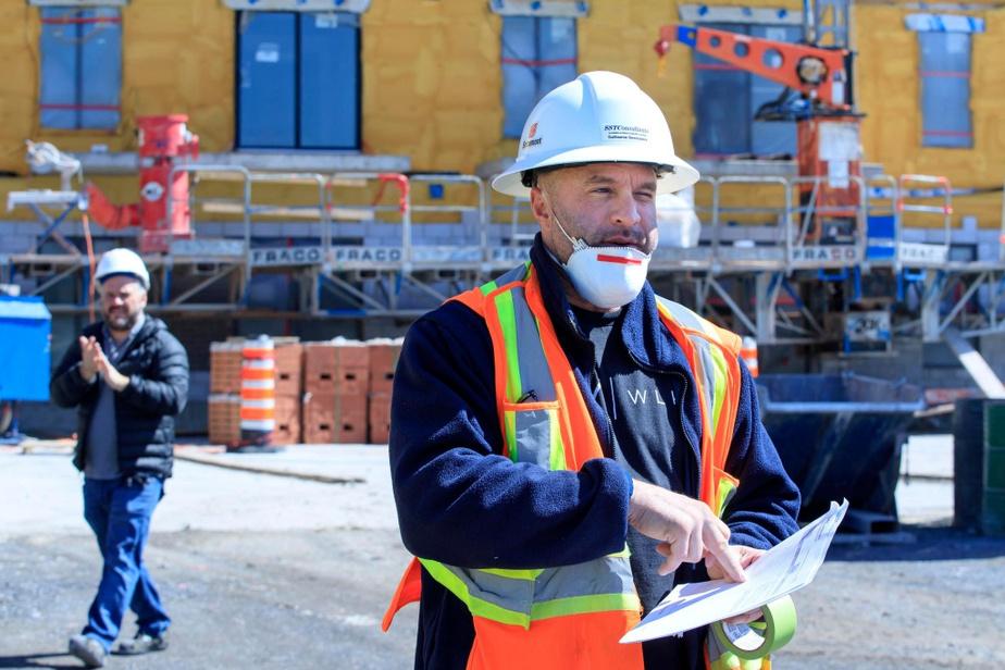 Le responsable de la santé et sécurité du chantier Livéo à Repentigny, Guillaume Desrosiers, donne les consignes d'usage. Au second plan, un travailleur consciencieux termine de se laver les mains.