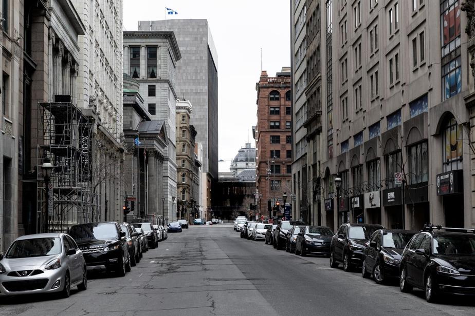 Midi, rue Saint-Jacques, dans le Vieux-Montréal. Habituellement grouillante de vie à cette heure de la journée, la rue est pour le moins dépeuplée.