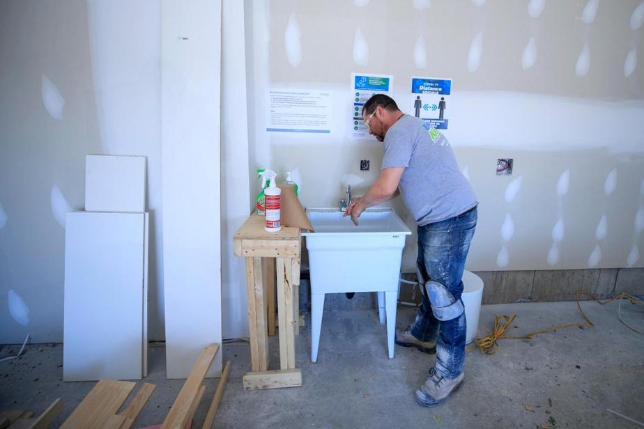 Jean-François Huard, carreleur, se lave les mains dans une station du chantier Lumicité Nature, rue Narbonne à Sainte-Julie.