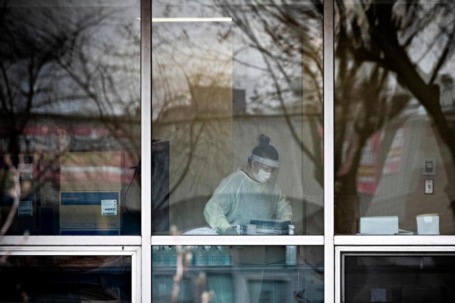 Une employée du CHSLD Sainte-Dorothée, à Laval, à travers les fenêtres de l'établissement qui a été durement touché par le coronavirus.