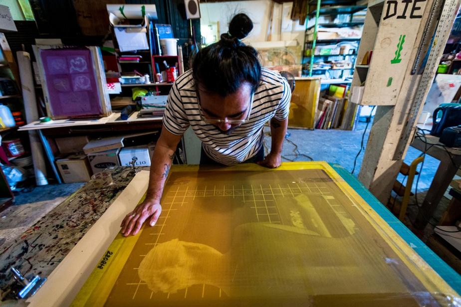 L'artiste inspecte une soie, afin de s'assurer qu'elle ne comporte pasd'imperfections.