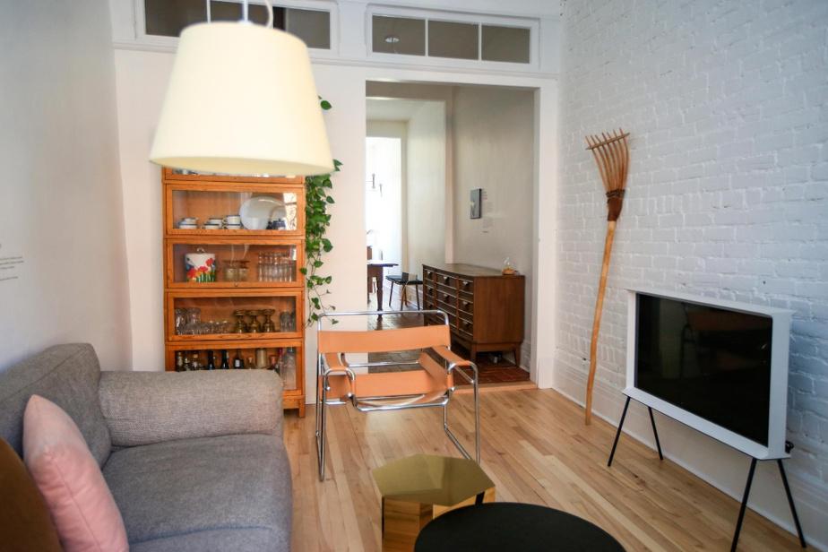 Le salon, ouvert sur le séjour, mêle des pièces anciennes et modernes comme une table d'appoint en laiton de Hay ou la télévision Sérif des frères Bouroullec pour Samsung.