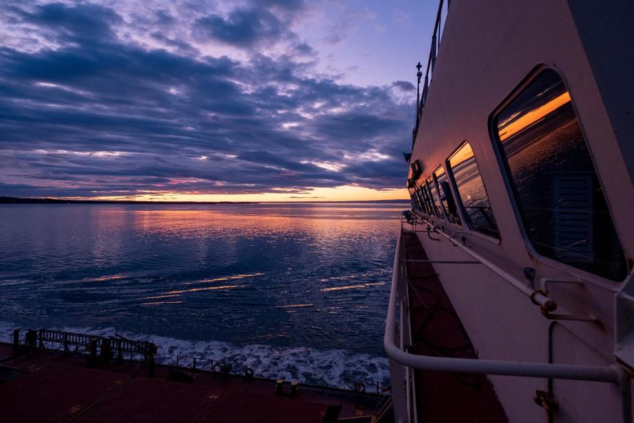 Le soleil se lève sur l'île aux Coudres, en aval de Québec, après un départ nocturne. Le navire progresse lentement, mais sans interruption.