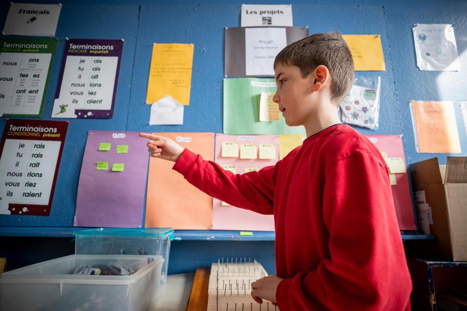 Julien montre le tableau de suivi de production de WowÉcolo, à côté d'une des tables de conjugaison de l'entreprise.