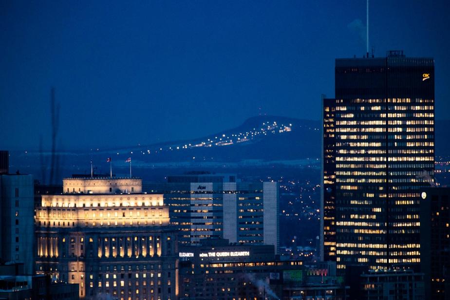 Les pistes illuminées du mont Saint-Bruno ponctuent l'horizon, entre les gratte-ciel de Montréal.