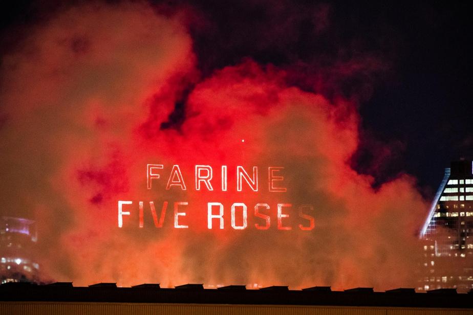 L'emblématique enseigne de Farine Five Roses apparaît derrière un mur de vapeur qui a pris la couleur des néons.