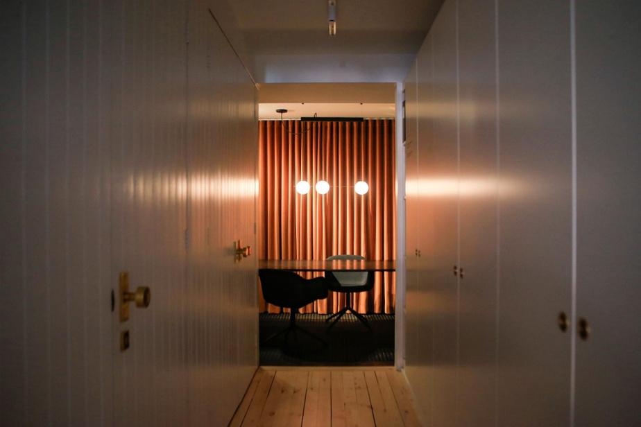 Avec ses murs de pierre, son rideau de velours terracotta et son luminaire sculptural signé Lambert&Fils, l'alcôve au bout du rez-de-chaussée est l'endroit parfait pour des réunions.